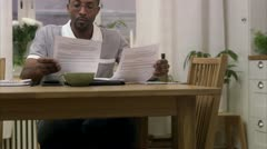 A man doing paper work at home Stock Footage