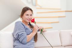 Young woman smelling a rose - stock photo