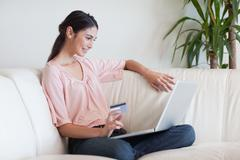Delighted woman shopping online - stock photo