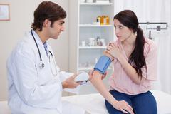 Doctor checking patients blood pressure - stock photo