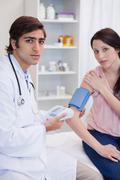 Stock Photo of Doctor examining patients blood pressure