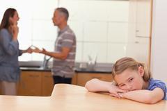 Sad girl hearing her parents fighting Stock Photos