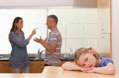 Sad little girl listening her parents having an argument - stock photo