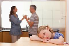 Sad girl hearing her parents arguing Stock Photos
