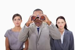 Businessman with colleagues using binoculars - stock photo