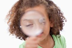 Stock Photo of Cute girl looking through a magnifying glass