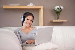Woman with notebook and headphones on the sofa - stock photo