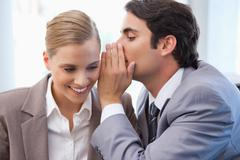 Businessman whispering something to his colleague Stock Photos
