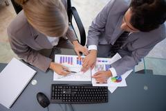 Serisous business team studying statistics - stock photo