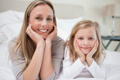 Smiling mother and daughter lying on the bed - stock photo