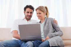 Stock Photo of Cute couple using a notebook