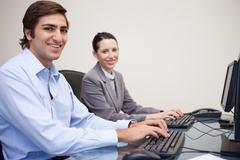 Side view of smiling colleagues working next to each other - stock photo