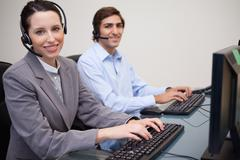 Side view of smiling call center agents at work - stock photo