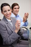 Side view of business team clapping while sitting at desk - stock photo