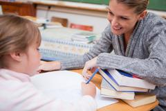 Schoolgirl writing with her smiling teacher - stock photo