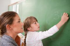 Teacher and a pupil making an addition - stock photo
