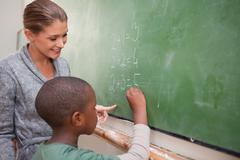 Cute teacher and a pupil making an addition - stock photo