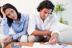 Stock Photo of Sad couple checking their bills