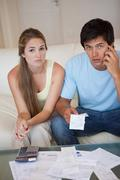 Portrait of a worried couple looking at their receipts - stock photo