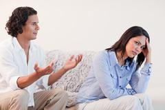 Man on the sofa trying to apologize to his girlfriend - stock photo