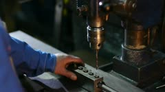 A worker does opening a drilling machine-tool in a metallic pipe at the plant Stock Footage