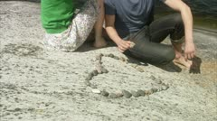 MS Couple making heart shape of pebbles on cliff, low section Stock Footage