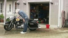 WS Senior man washing Harley Davidson in front of suburban house - stock footage