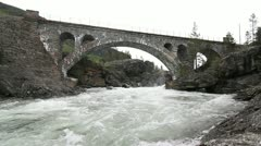 Old stone bridge crossing waterfall Stock Footage