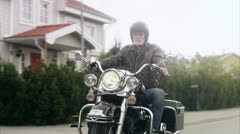 REAR POV Senior man riding Harley Davidson on suburban road Stock Footage