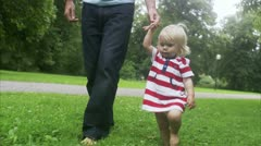 MS Father walking with daughter across park Stock Footage