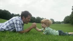 MS Father and son arm-wrestling on grass Stock Footage