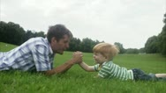 Stock Video Footage of MS Father and son arm-wrestling on grass