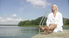 WS Woman relaxing on jetty Stock Footage