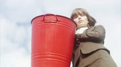 MS LA Businesswoman emptying recycle bin against sky Stock Footage