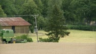 WS Combine harvester on field, barn in background Stock Footage