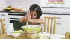MS Girl mixing ingredients in bowl at kitchen counter, two sisters tasting - stock footage