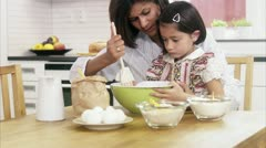 MS Mother helping daughter mixing ingredients in bowl at kitchen counter Stock Footage