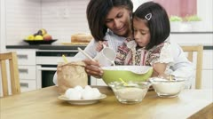 MS Mother helping daughter mixing ingredients in bowl at kitchen counter - stock footage
