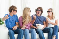 Friends laugh and joke around while watching a movie - stock photo