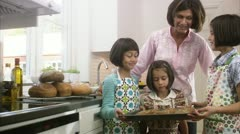 MS Woman with three girls holding baking tray in kitchen Stock Footage