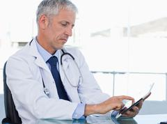 Serious doctor working with a tablet computer - stock photo