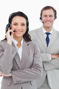 Smiling call center agents with headsets on and arms folded Stock Photos