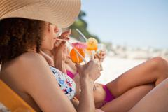 Stock Photo of Side view of a beautiful woman sipping her cocktail accompanied by her friend