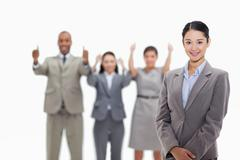 Stock Photo of Businesswoman smiling with co-workers approving in the background