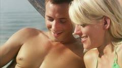 CU Couple sunbathing by lake Stock Footage