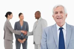 Mature salesman with trading partners behind him - stock photo