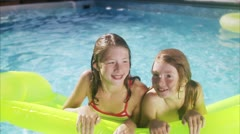 MS Sisters swimming on airbeds in swimming pool Stock Footage