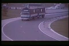 Car following truck off main highway Stock Footage