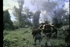 Rear view of troops running up hill toward smoke Stock Footage
