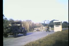 Military jeep driving through  road block Stock Footage
